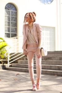 mulher usando terninho em tom rosa pastel com vários acessórios e tenis rose também.
