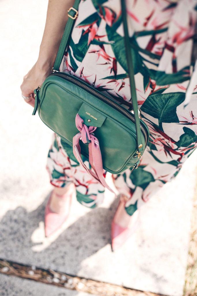 vestido estampado em tons de verde e rosa claro combinando com bolsa verde. look de cores intensas e belíssimo