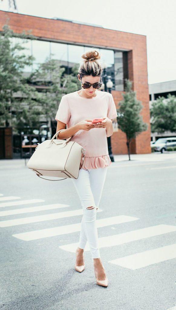 muler atravessando a rua com roupa em tons claros, rosa pastel, blush, calca branca, olhando no celular