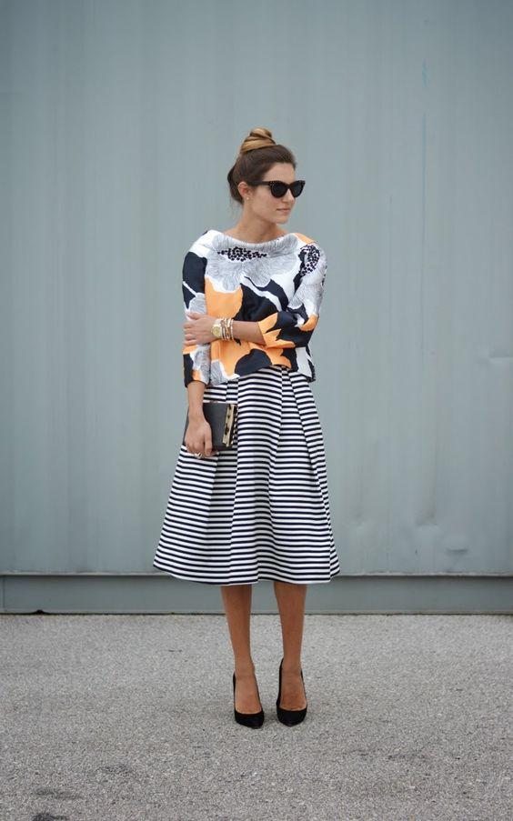 mulher usando saia midi godê listrada em preto e branco com blusa em oputra estampa. mix'n match, mistura de estampas, saia listrada, blusa florida