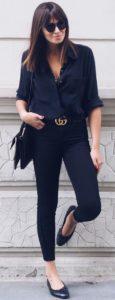 mulher elegante de calça jeans skinny preta e camisa preta com oculos escuros e sapatilha.