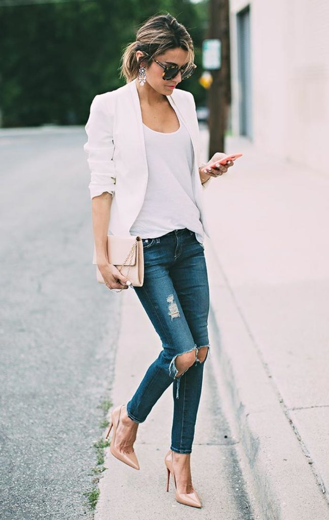 mulher travessando a rua com celular na mão usando calça jeans destroyed rasgada, blazer branco e scarpin tom da pele nude.