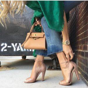 mulher arrumando o sapato nude com detalhes em tachas na parte de tras.